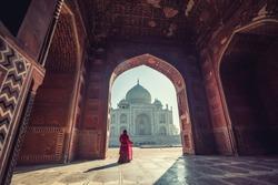 Beautiful woman in traditional dress costume,Asian woman wearing typical saree/sari dress identity culture of India. Taj Mahal Scenic The morning view of Taj Mahal monument  at Agra, India.