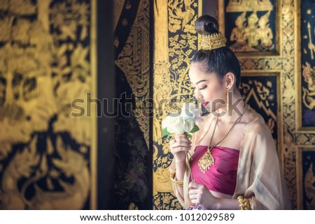 Beautiful woman in traditional dress costume,Asian woman wearing typical Thai dress identity culture of Thailand #1012029589