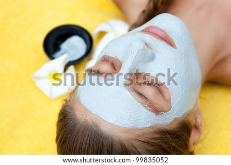 Beautiful woman in tropical spa making face mask and other treatments