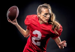 Beautiful woman in uniform playing american football with ball isolated on black