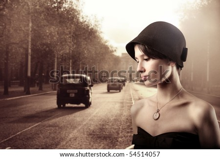 Beautiful woman in vintage clothes with street on the background