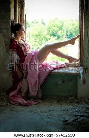 beautiful woman in vintage dress sitting on the window