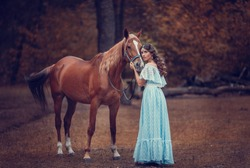 Beautiful woman in vintage dress with a romantic bay horse in the park