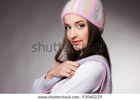 beautiful woman in warm clothing on gray background