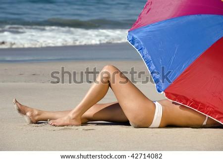 beautiful woman in white bikini on tropical beach under colorful umbrella