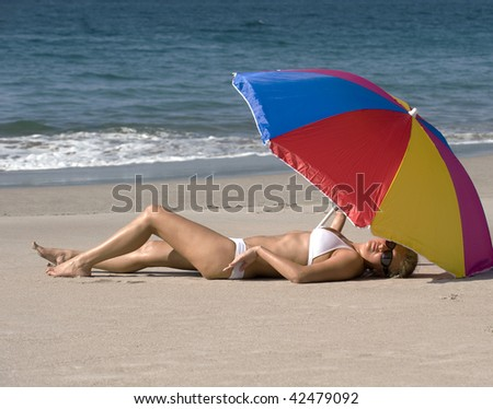 beautiful woman in white bikini relaxing under colorful umbrella on tropical beach