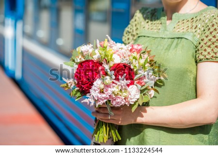 Stock Photo Beautiful woman in white coat with red roses in hand