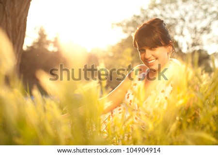 Beautiful woman in white dress at summer sunset.