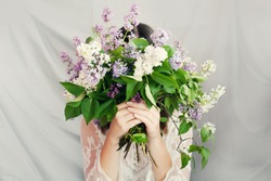 Beautiful woman in white dress hid her face behind large lilac bouquet