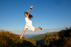 Beautiful woman in white dress running in the mountains. Jumping on mountain peak rock. Beautiful girl looking happy and smiling. Relaxing, feeling alive, breathing fresh air, got freedom from work
