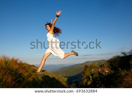 Beautiful woman in white dress running in the mountains. Jumping on mountain peak rock. Beautiful girl looking happy and smiling. Relaxing, feeling alive, breathing fresh air, got freedom from work #693632884