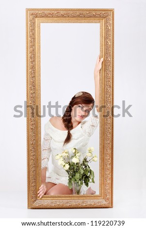 Beautiful woman in white openwork dress sits on floor behind big frame near vase with dry roses.