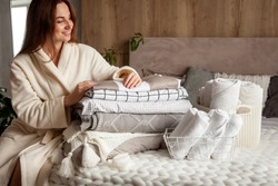 Beautiful woman in winter thick warm robe is sitting and neatly folding bed linens and white bath towels. Organizing and sorting clean laundry. Organic and natural cotton textile. Manufacture.