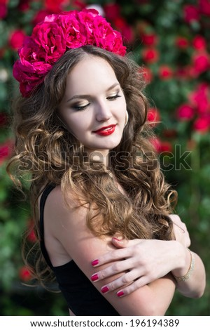 Beautiful woman in wreath in the garden of  roses
