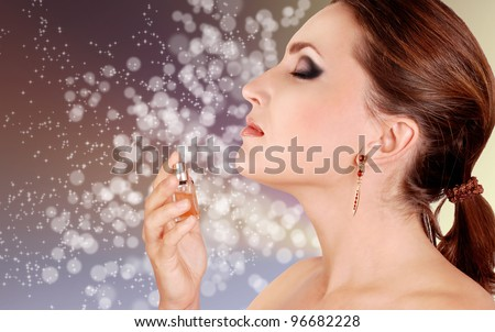 Beautiful woman inhales with pleasure perfume aroma