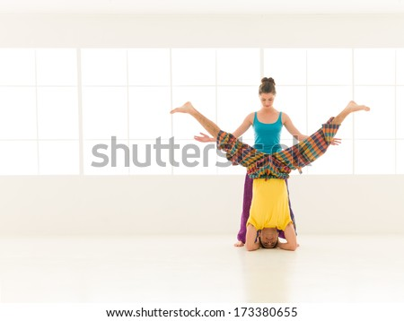 beautiful woman instructor with a handsome man dressed in vibrant colors are partners yoga in white gym