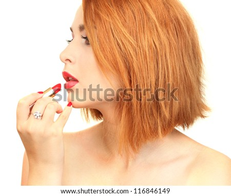beautiful woman is applying her lips with red lipstick