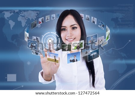 Beautiful woman is clicking on touch screen to choose digital photos