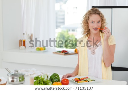 Beautiful woman is eating vegetables at home