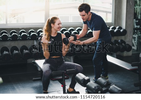 Beautiful woman is exercising and fitness. The trainer gives instructions on how to exercise in the gym. #1154720116