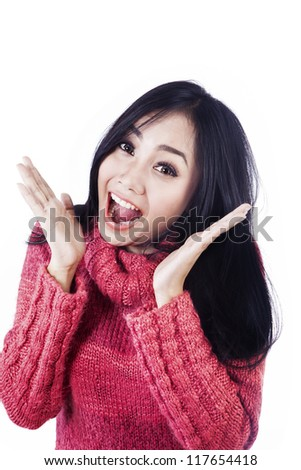 Beautiful woman is expressing her surprise happily wearing pink jumper isolated in white