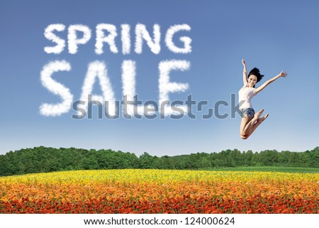 Beautiful woman is jumping over colorful flowers during spring sale