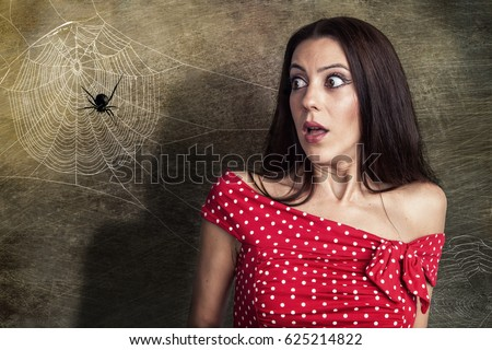 Beautiful woman is looking shocked to a spider next to her face