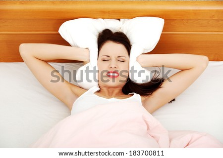 Beautiful woman is lying in bed and covering her ears with pillow. Noise or insomnia concept.