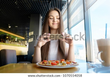 beautiful woman is making photo of food in cafe, latte on table pizza, communication in social networks