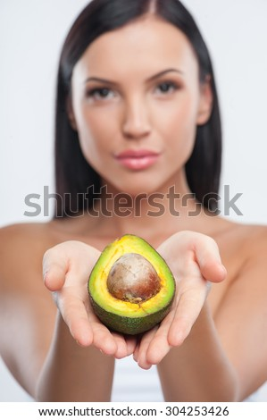 Beautiful woman is presenting an avocado. She is holding it in her palms. She is looking at the camera with confidence. Focus on avocado and isolated