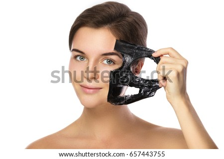 Beautiful woman is removing purifying mask from her face over white background #657443755