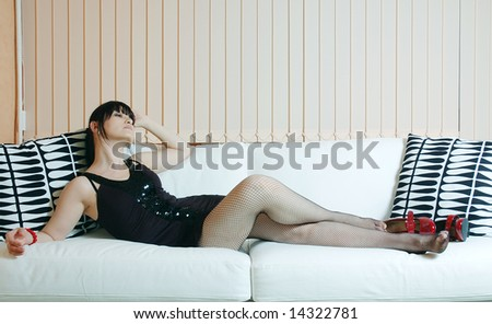 beautiful woman is resting on the white sofa