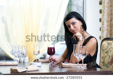 Beautiful woman is sitting in restaurant with glass of red wine