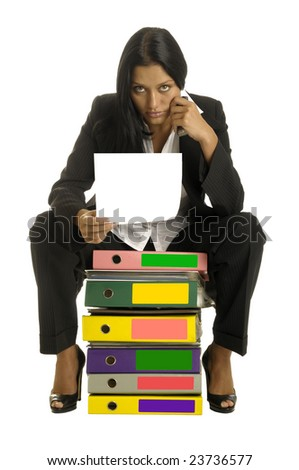 Beautiful woman is sitting on the  heap of binders and reading the document