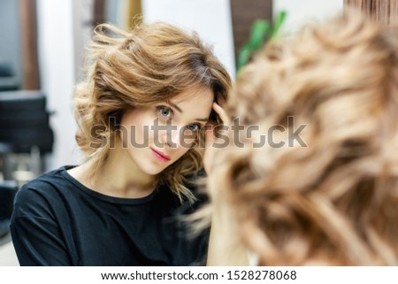 Beautiful woman is touching her hair and looking at her reflection in the mirror in beauty salon. Beauty concept. #1528278068