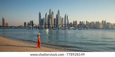 Beautiful woman is walking on the beach and looking to Dubai Marina Skyline #778928149