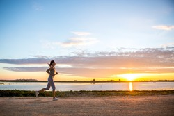 Beautiful woman jogging in the morning above the dam at the sky sunset.