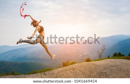 Beautiful woman jumper on High mountain. at sunrise. #1041669454