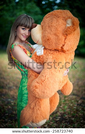 beautiful woman keeps big and orange toy teddy bear. outdoors in the park