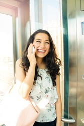 Beautiful woman laughing at cell phone inside an elevator