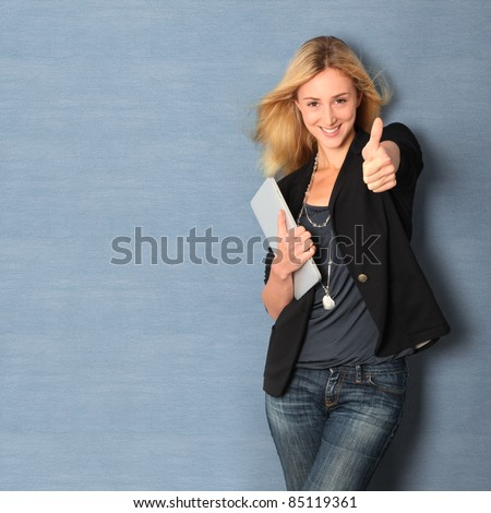 Beautiful woman leaning on wall with touchpad