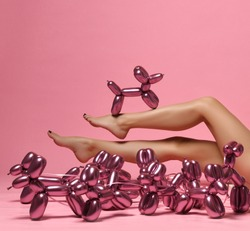 Beautiful woman legs and metallic dog balloon composition on pink background