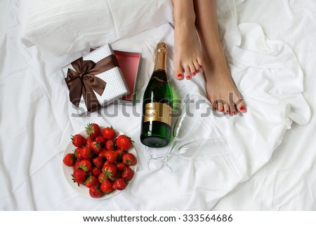 beautiful woman legs in bed romantic morning gift strawberry champagne Top view