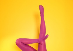 Beautiful woman legs in color tights on yellow background