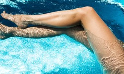 Beautiful woman legs in swimming pool.
