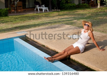 beautiful woman legs, sunbathing, woman in sunglasses enjoying the sun near swimming pool