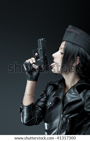 Beautiful woman licking black handgun