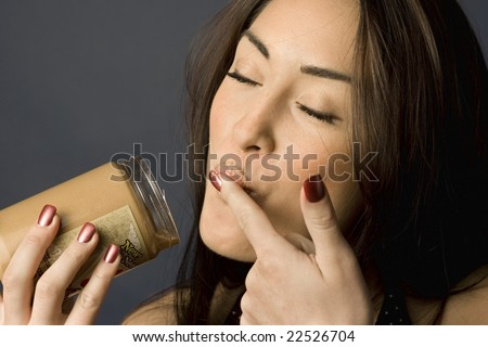 Beautiful woman licking peanut butter off her finger