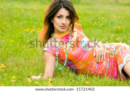 Beautiful woman lies on a grass in the field