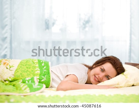 beautiful woman lies on pillow in bed